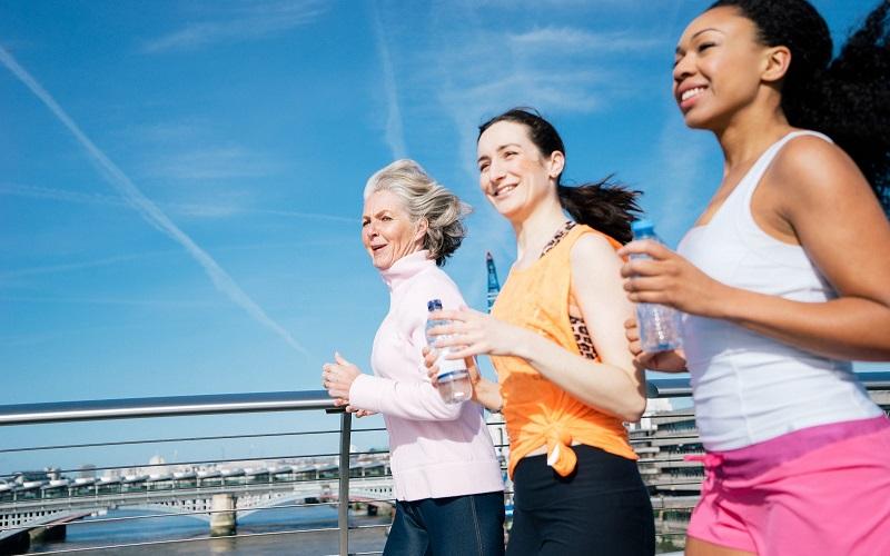 Three women jogging by a marina.