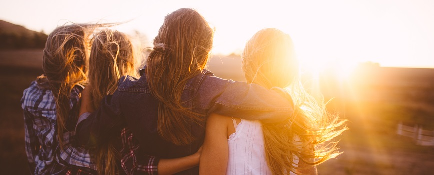 A group of young women embracing while watching a sunset.