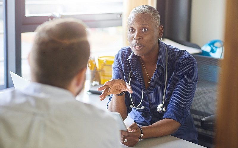 A female doctor talks with a male patient.