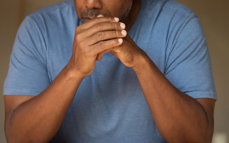 A male adult of African-American race sits at a table, with hands clasped, in a display of anxiety.