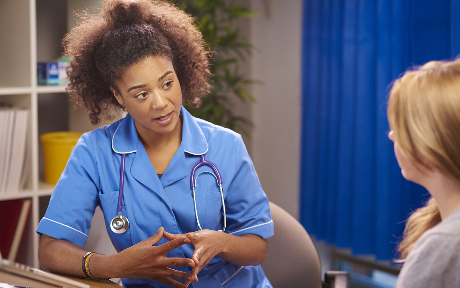 An African-American clinician explains medical terms to a white female patient.