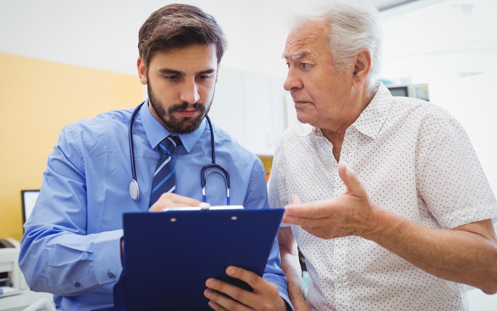 An elderly male patient consulting with a male physician.