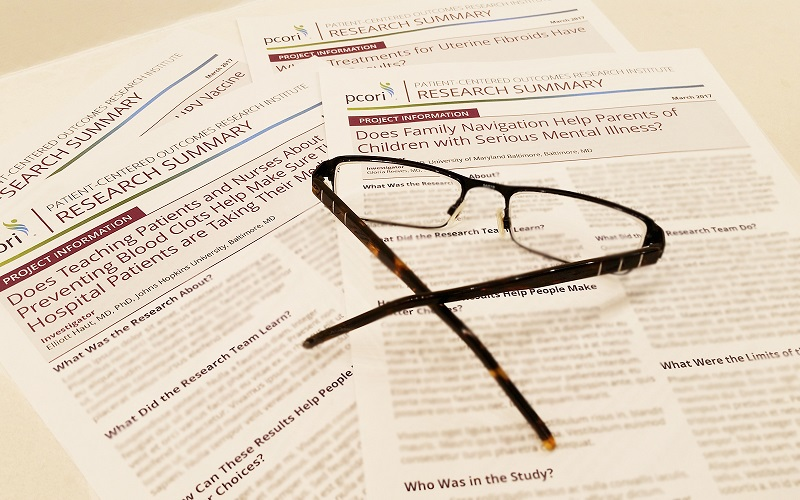 A handful of PCORI-funded research summary handouts laid out on a table.