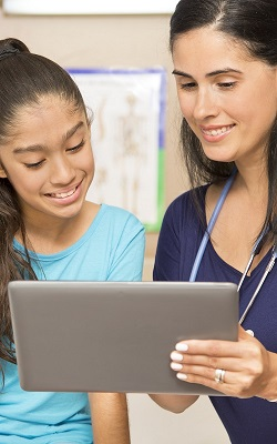 A young Hispanic girl discussing her medical records with a nurse.
