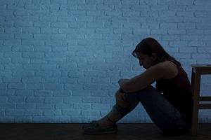 A woman's silhouette against a blue wall