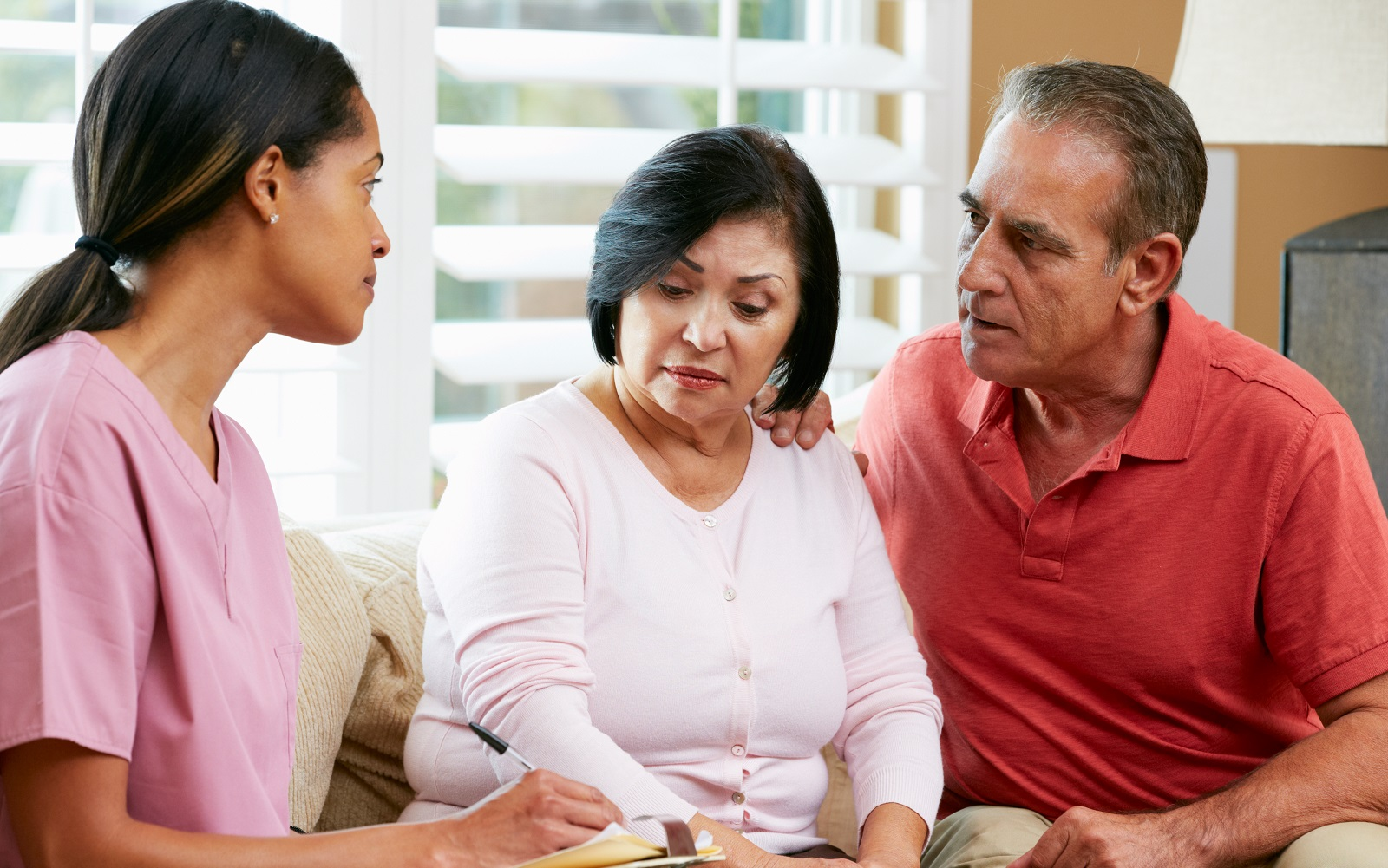 A female African-American nurse speaking with an older Latino couple and taking notes.
