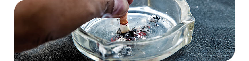 An image of a hand squashing a cigarette bud into an ashtray.