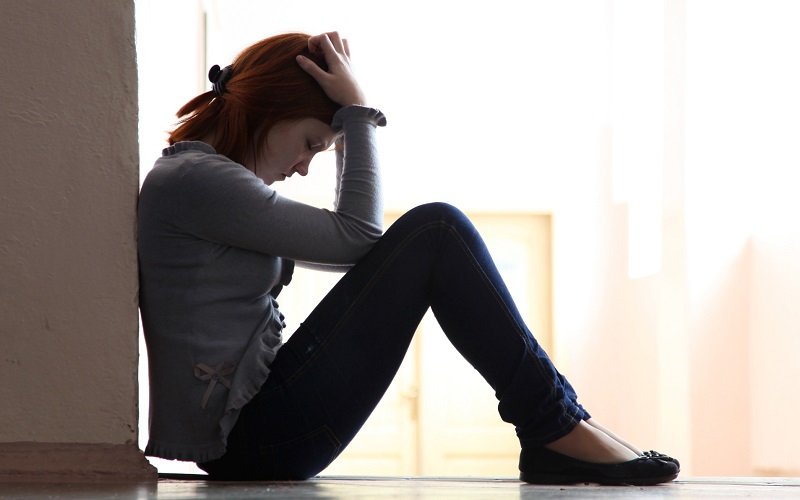 A woman sitting on the floor, leaning against a wall, in sadness.