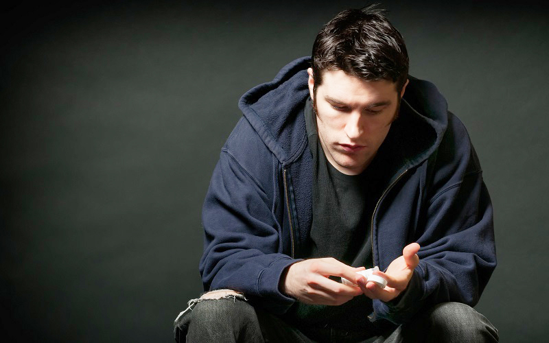 Depressed young caucasian man holding a prescription medication.
