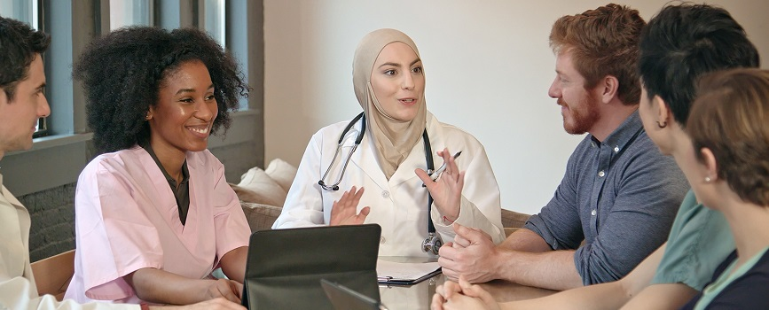 A Muslim doctor talks to a group of people.