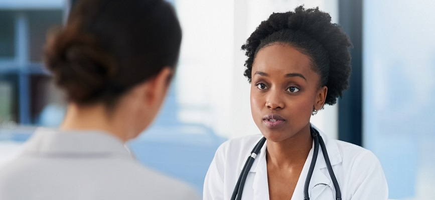 An African-American doctor speaking with a female patient