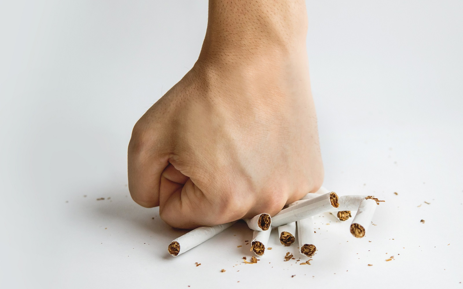 A hand crushing several unlit cigarettes on a table.