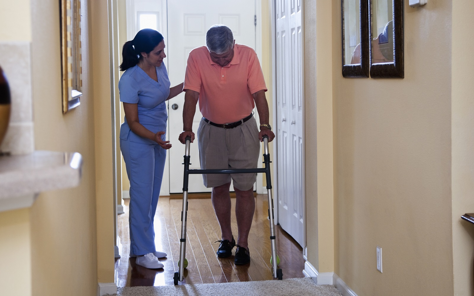 A female home health aide in a blue uniform assists a man using a walker.
