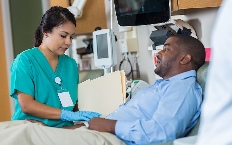 A Hispanic nurse attending to a male African American patient.