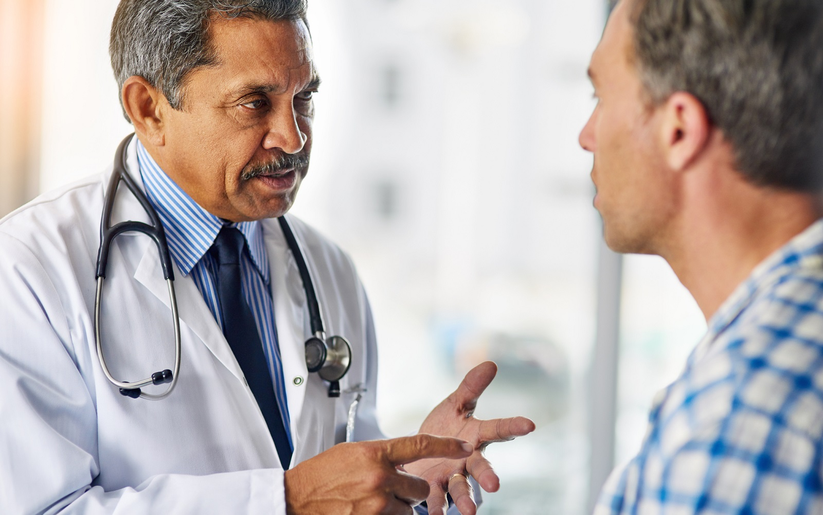 A male doctor giving advice to a male patient.