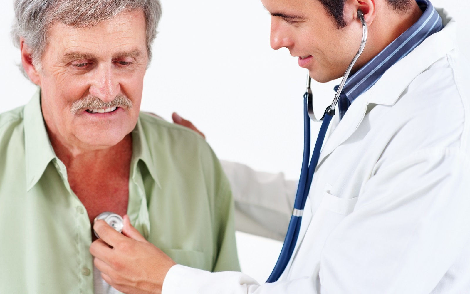 A male doctor listening to a senior man's chest with a stethoscope.