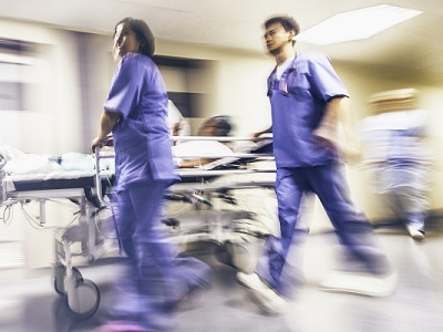 Medical Personnel Running Alongside a Patient in Hospital Bed