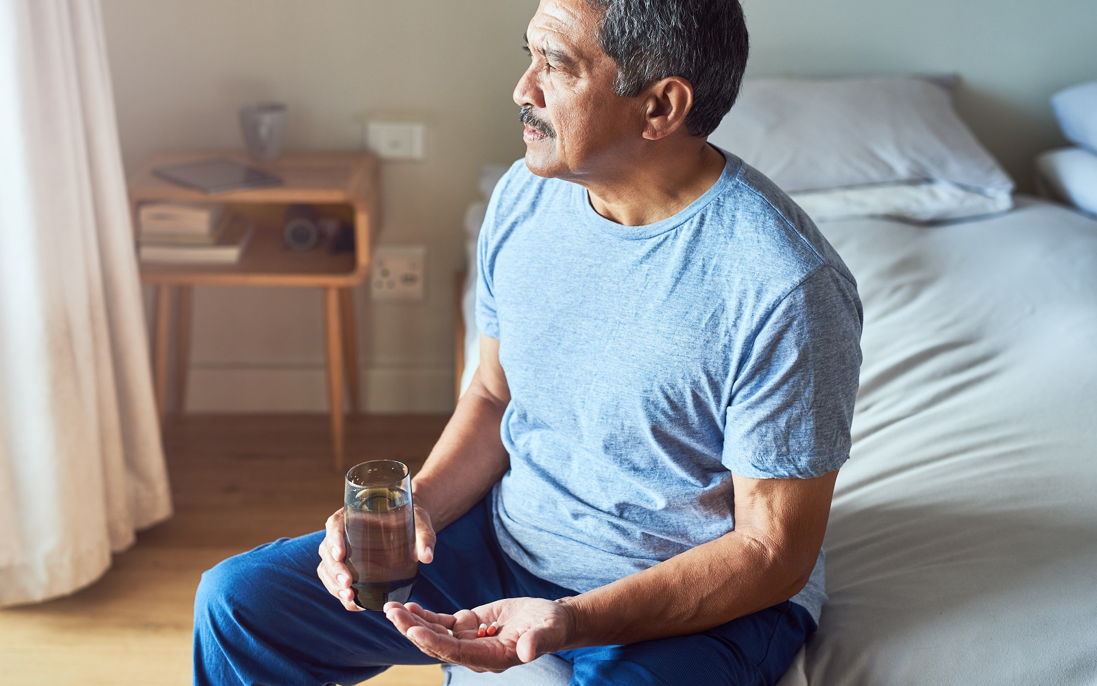 Older Male Sitting By Side of Bed Looking Sad With Pills In His Hand.