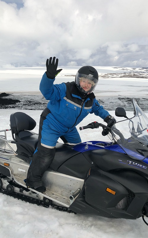 Amy Berman, RN, Senior Program Officer, The John A. Hartford Foundation, stands and waves while on a snowmobile.