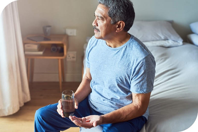 Older Male Sitting By Side of Bed Looking Sad With Pills In His Hand