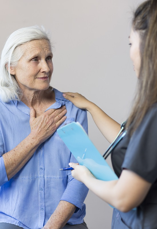 Image for the PCORI Evidence Updates on Stroke Atrial Fibrillation for Clinicians An older white woman in a consultation office, as she holds a hand to her chest and looks uncomfortable, while speaking to a female medical professional.