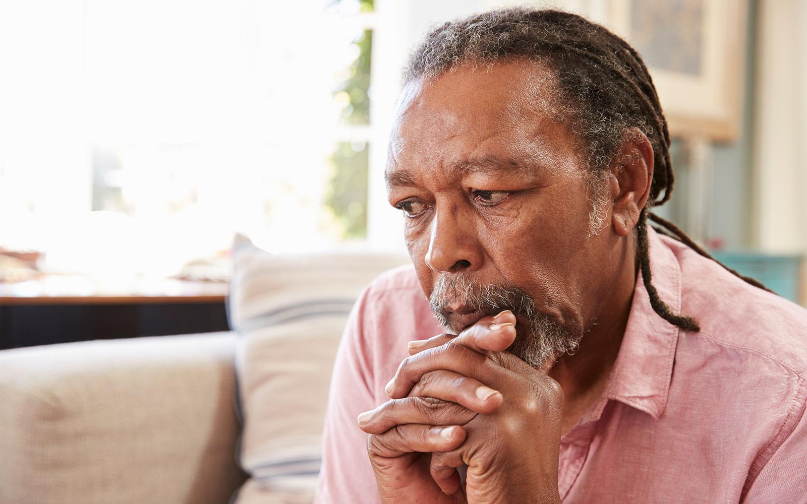 A senior African-American male seated on a couch, resting his head on his fists, in deep thought.