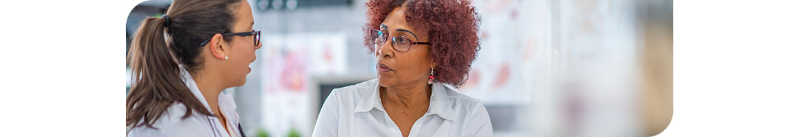 An elderly african-american women in a clinic speaking a female medical professional.