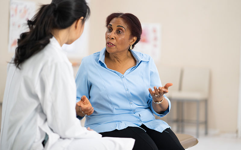 An older woman of African descent is discussing health issues with a female medical professional in a clinical setting.
