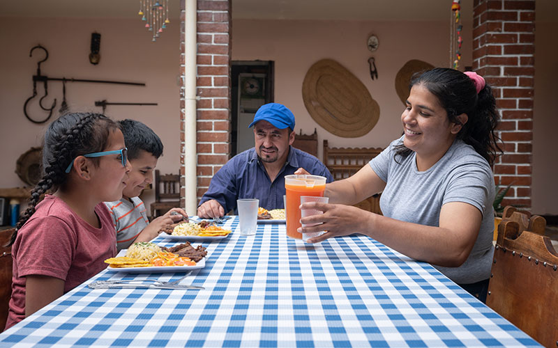 Four members of a Hispanic/Latino family seated at a dining table having a meal together