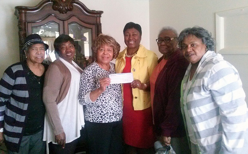 Members of a civic organization that raises money to help families in need present a donation to Freddie White-Johnson for the Fannie Lou Hamer Cancer Foundation.