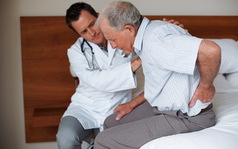 A doctor cares for an elderly male patient.