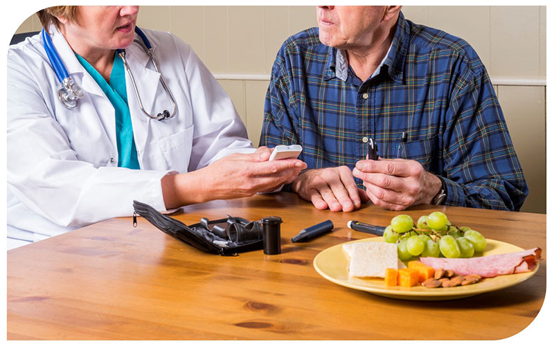 An older white male seated next to a female medical professional discuss the finger stick process for checking blood sugar levels for people with diabetes.