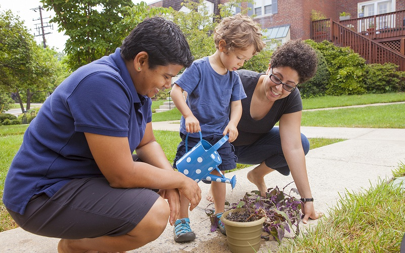 A female same-sex couple with their child, in the garden, watching the little boy water a pot of plants.