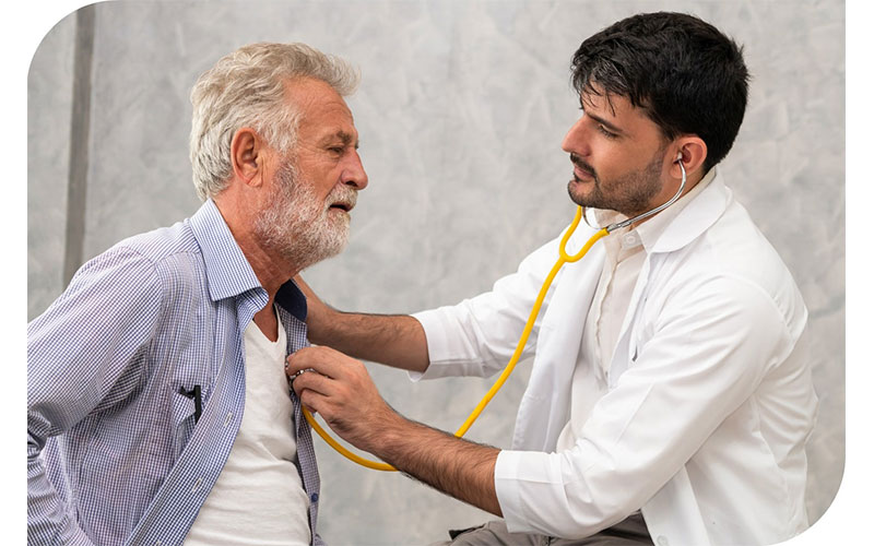 Male Medical Professional Listens to Heart of Older Male Patient With Stethoscope