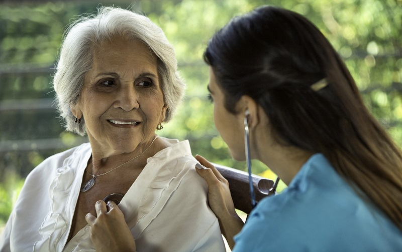 A young female physician holds a stethoscope to an older female's chest.