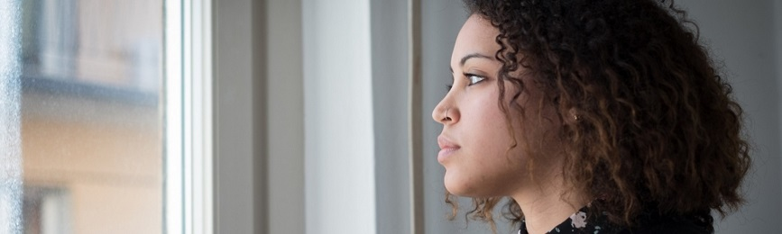 A young woman looks out a window.