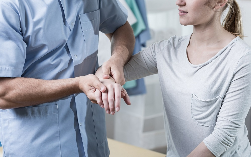 A woman with a painful wrist being examined by a medical professional.