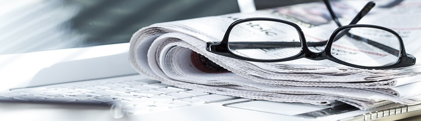 A pair of eyeglasses sitting on a rolled newspaper on top of a laptop keyboard.