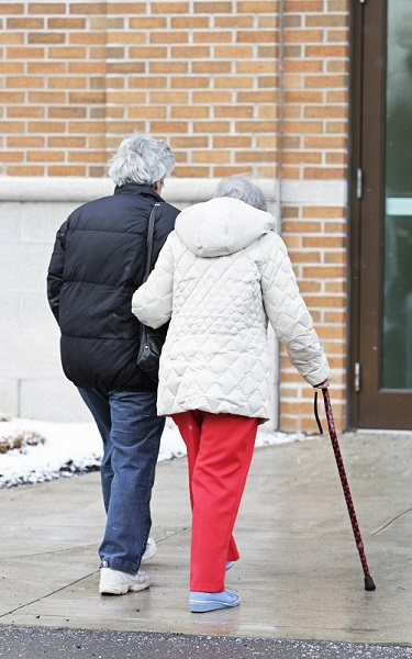 Elderly Woman Walking With Cane Supported By Caregiver