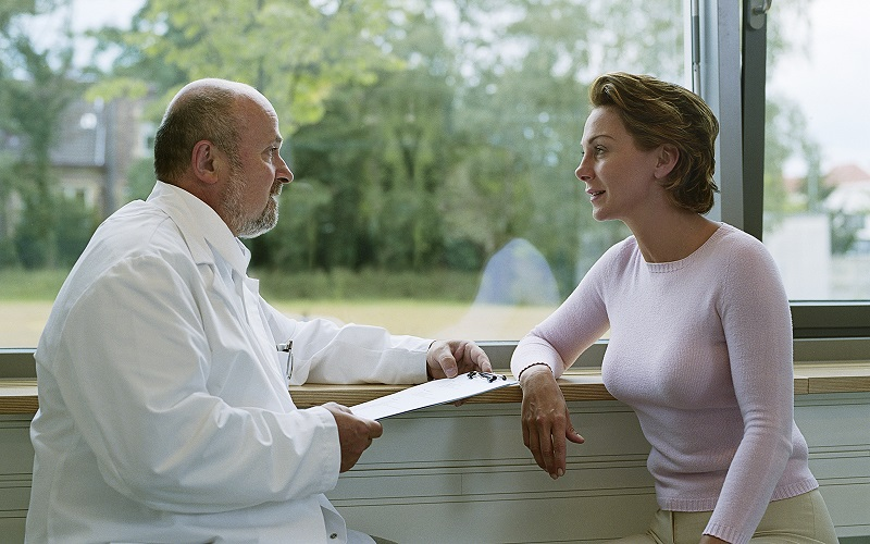 A male physician speaks to a female patient.