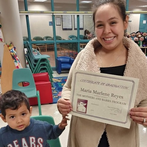 Maria Marlene Reyes, with her three-year-old son, proudly holds her certificate after completing the Mothers and Babies Program as part of the PCORI-funded study. She is expecting her second child. (Photo courtesy of Jessica Johnson)