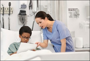 A young boy in a hospital bed discusses a report with a female medical professional