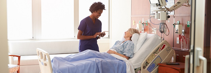 African American Female Nurse Speaking With Female Patient