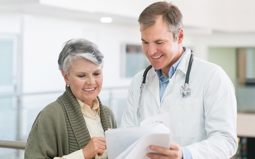 An older white woman discussing her medical records with a male doctor.