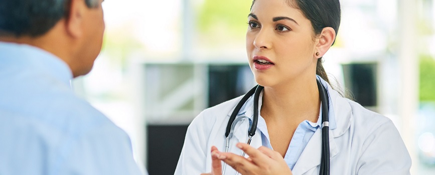 A young female doctor gives an older male patient advice during a consultation.