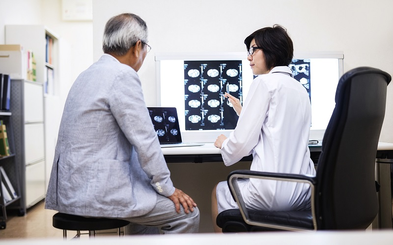 An older Asian man discusses MRI images with a female Asian doctor.