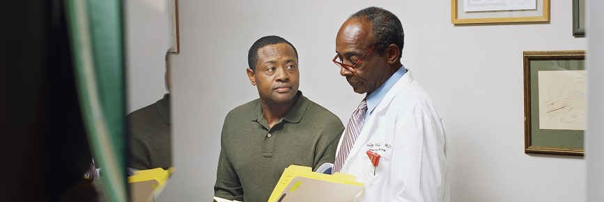 An African-American doctor discussing records with an older African-American male patient.