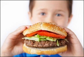 A young boy holding a hamburger, for the pediatric obesity blog post in September 2016