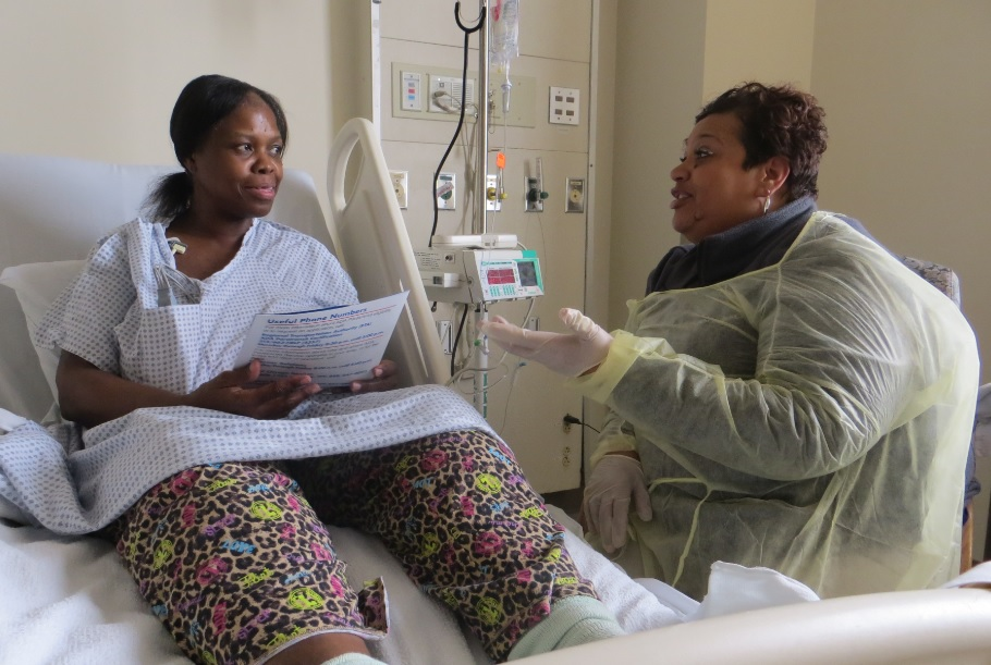 An African-American nurse discusses paperwork with a patient.
