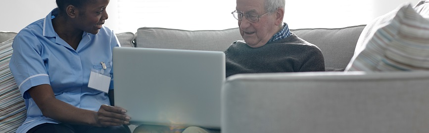 Female caregiver sitting with a senior man using laptop while at home.